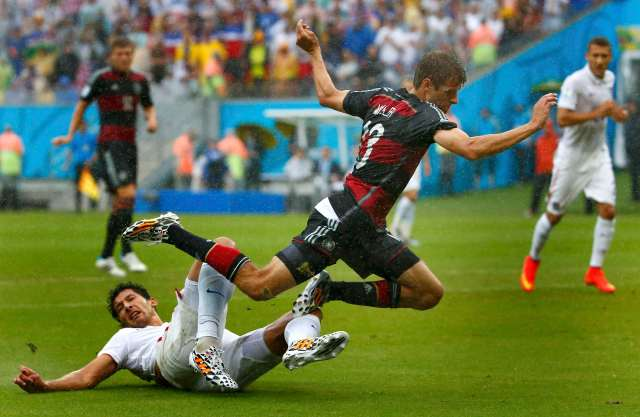 Omar Gonzalez of the U.S. (in white) tackles Germany's Thomas Mueller. (REUTERS/Tony Gentile)