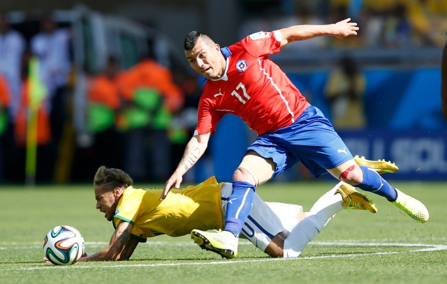 Brazil's Neymar (bottom) falls under pressure as he fights for the ball with Chile's Gary Medel. (REUTERS/Toru Hanai)