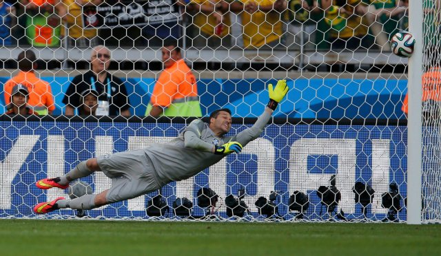 Brazil's Julio Cesar dives as the ball shot by Chile's Gonzalo Jara (unseen) rebounds off the post to decide their penalty shootout. (REUTERS/Sergio Perez)