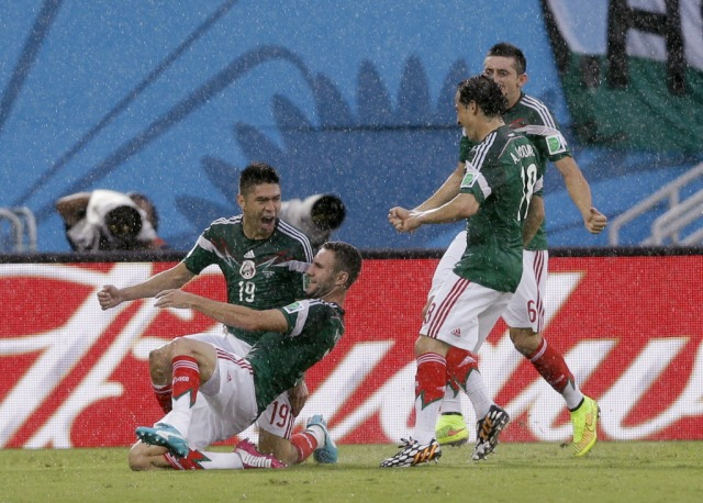 Mexico's Oribe Peralta, left, celebrates with teammates after scoring the opening goal. (Ricardo Mazalan, AP Photo)