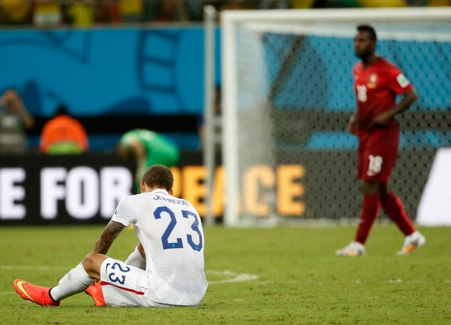 United States defender Fabian Johnson (23) sits on the ground after the final whistle as Portugal forward Varela (18), who scored the tying goal, walks past. (Winslow Townson, USA TODAY Sports)