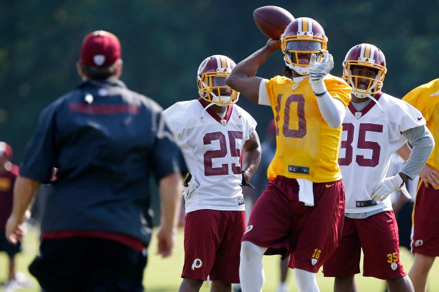 Redskins QB Robert Griffin III (10) remain more composed than some of his teammates in the Ashburn, Va., heat Tuesday. (Geoff Burke, USA TODAY Sports)