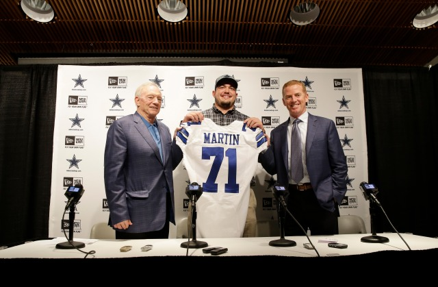 Dallas Cowboys draft pick Zach Martin, center, poses for photos with team owner Jerry Jones, left, and head coach Jason Garrett at Valley Ranch in Irving, Texas, Saturday, May 10, 2014. Martin, a Notre Dame offensive tackle, will forever be known as the player the Cowboys drafted instead of Johnny Manziel. (AP Photo/LM Otero)
