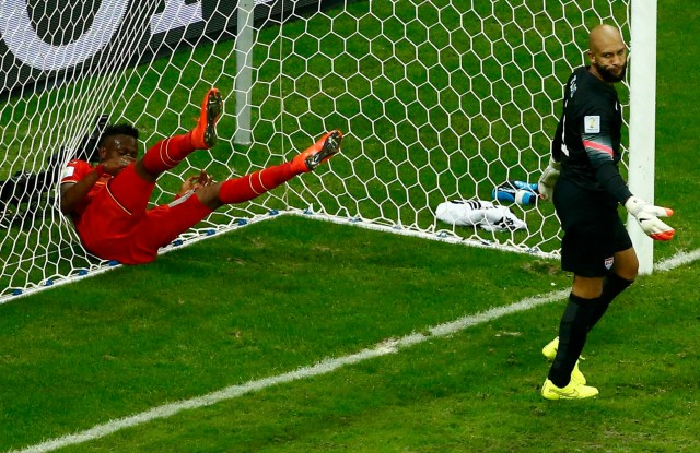 Belgium's Divock Origi throws himself into the goal net, behind goalkeeper Tim Howard of the U.S, after missing an opportunity to score a goal. (REUTERS/Ruben Sprich)