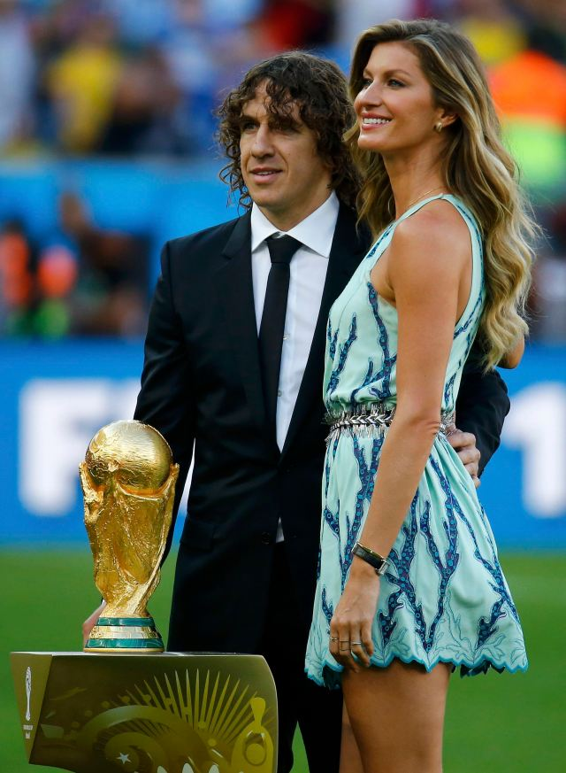 Retired footballer Carles Puyol of Spain (L), a member of the 2010 World Cup winning team, and Brazilian supermodel Gisele Bundchen pose with the World Cup trophy. (REUTERS/Kai Pfaffenbach)