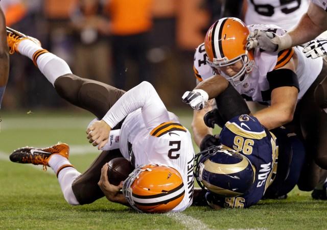 Cleveland Browns quarterback Johnny Manziel (2) is sacked by St. Louis Rams defensive end Michael Sam (96). (AP Photo/Tony Dejak)