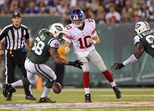 New York Giants quarterback Eli Manning (10) has the ball stripped by New York Jets defensive end Jason Babin. (Adam Hunger-USA TODAY Sports)