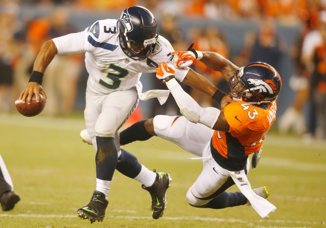 Seahawks QB Russell Wilson gets harassed by Broncos S T.J. Ward on Thursday night. (Chris Humphreys-USA TODAY Sports)