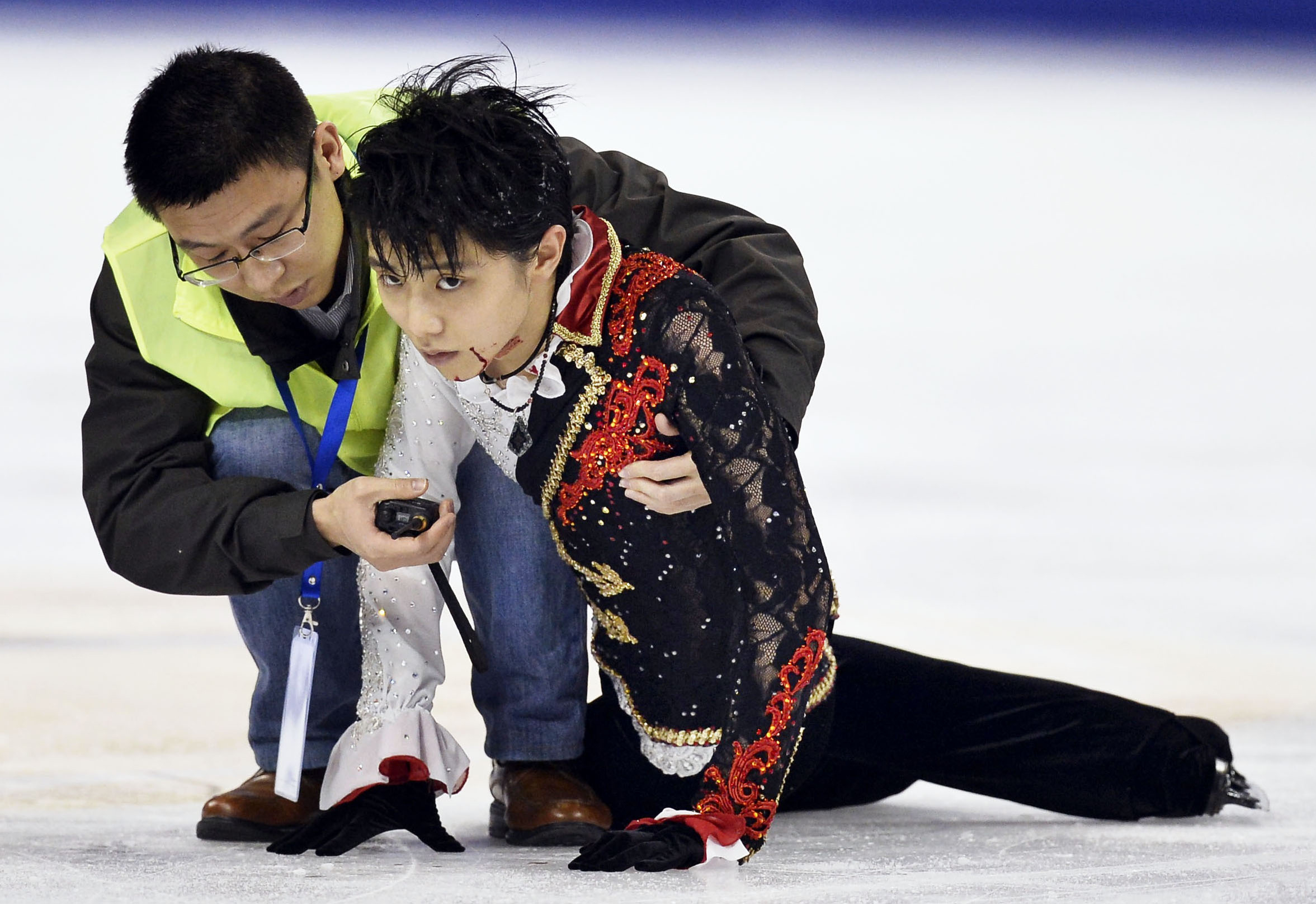 Yuzuru Hanyu of Japan is helped by a medical team member.  (AP Photo/Kyodo News)
