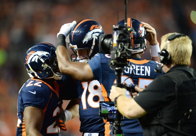 Broncos running back C.J. Anderson (22) and tight end Virgil Green (85) celebrate with quarterback Peyton Manning (18) after his record setting 509th career touchdown pass. (Ron Chenoy-USA TODAY Sports)
