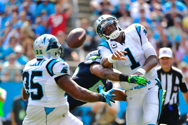 Carolina Panthers quarterback Cam Newton (1) passes the ball to fullback Mike Tolbert (35) as he is hit by Seattle Seahawks middle linebacker Bobby Wagner (54) in 2013. (Bob Donnan-USA TODAY Sports)