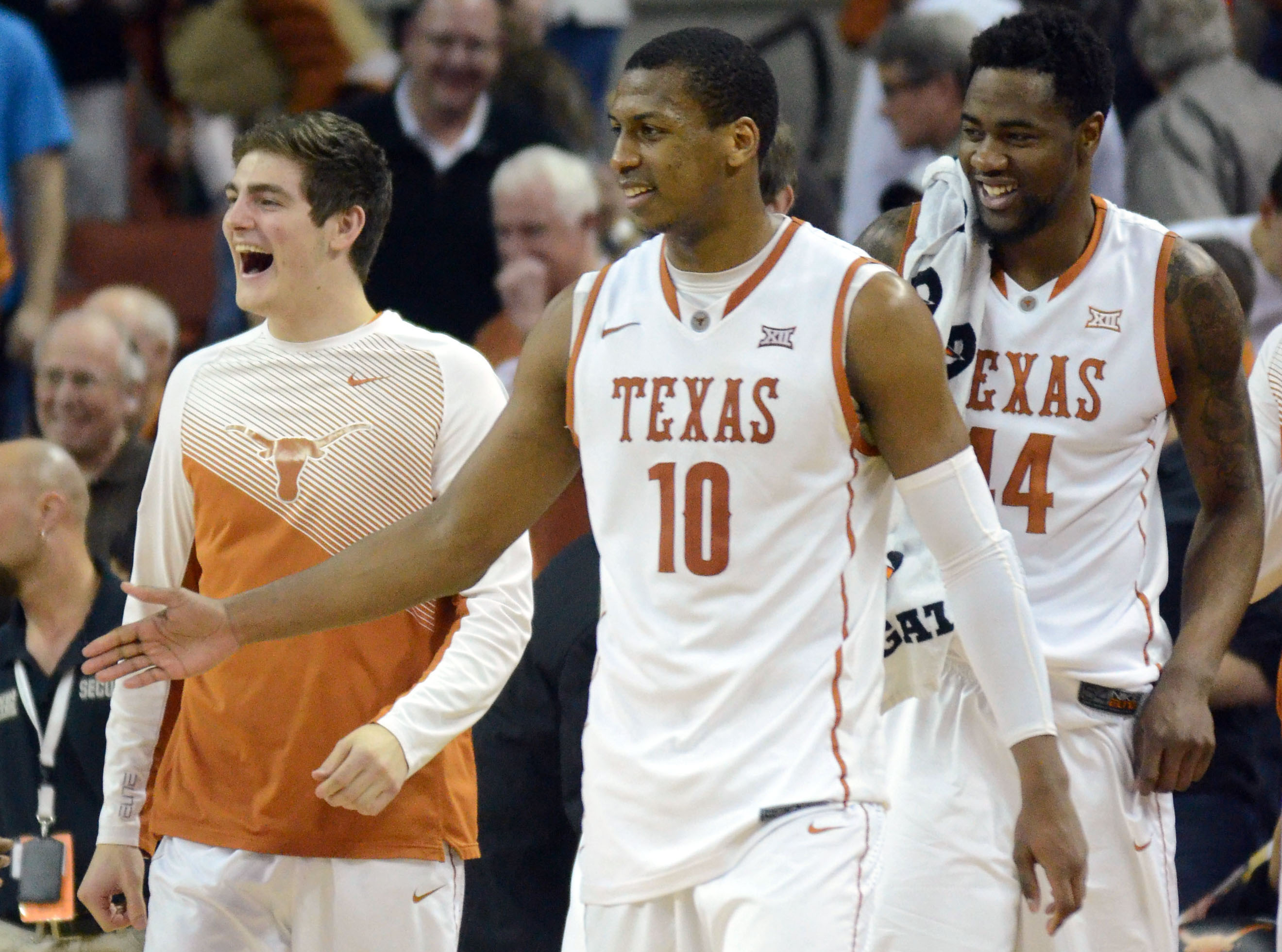 Texas' Jonathan Holmes (center) celebrates a midseason win vs. Kansas State with teammates Ryan McClurg (left) and Prince Ibeh (right). Brendan Maloney / USA TODAY Sports