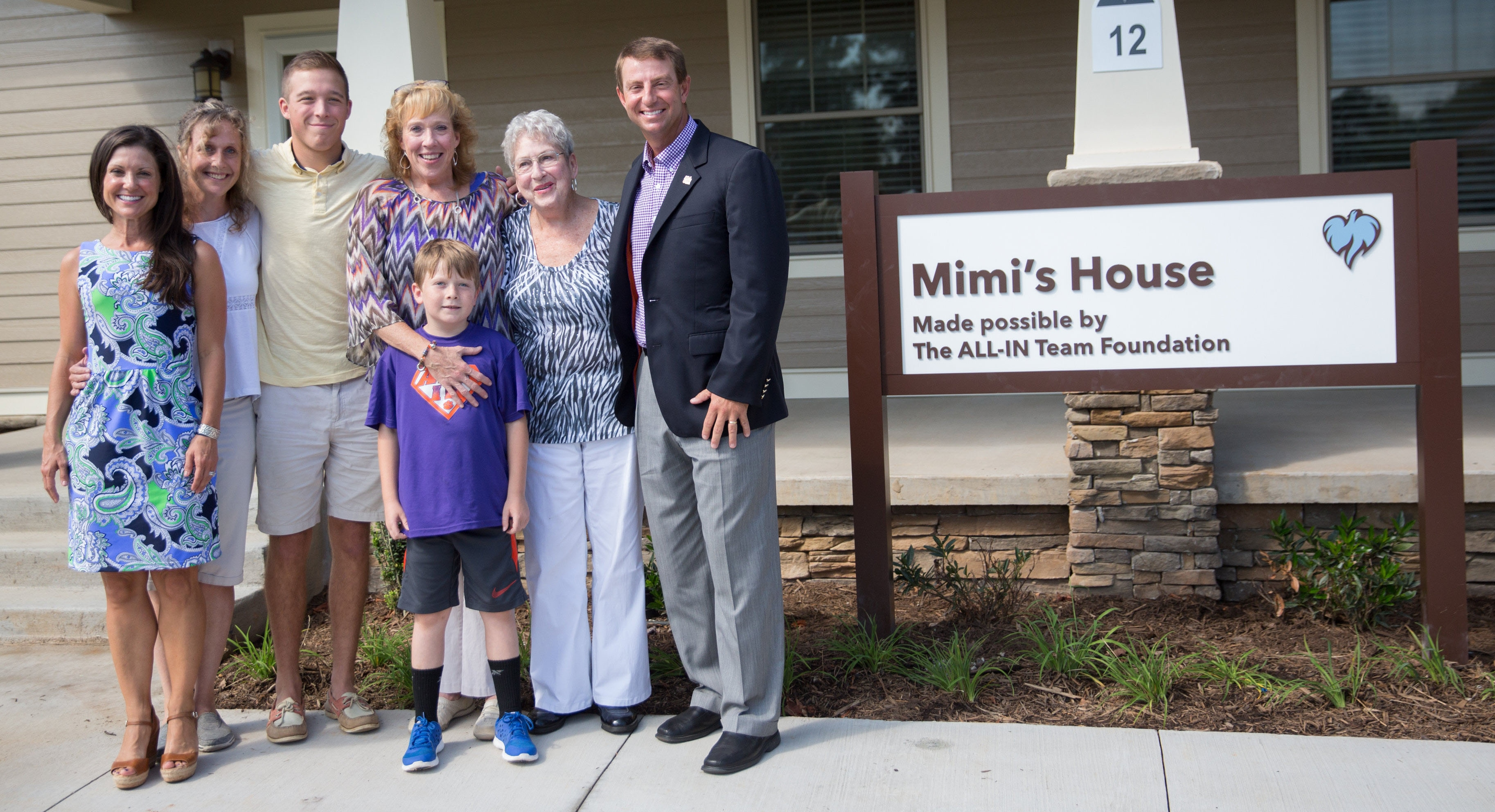 Clemson head coach Dabo Swinney (far right) and Kalthleen Swinney (far left), surprised family friend Mimi Metcalfe (fourth from the left) by naming the new safe house at Serenity Place in her honor.