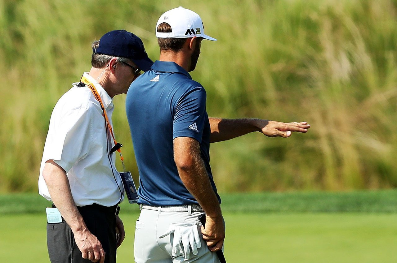 Dustin Johnson talks with a rules official on Oakmont's fifth green during the final round of the U.S. Open.