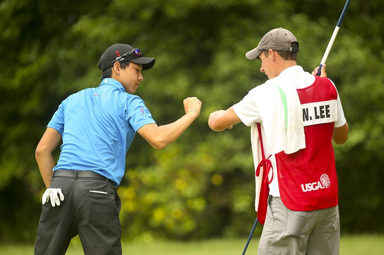 Min Woo Lee celebrates a putt on the 13th hole with his caddie in the final round of match play during the 2016 U.S. Junior Amateur at The Honors Course in Ooltewah, Tenn.