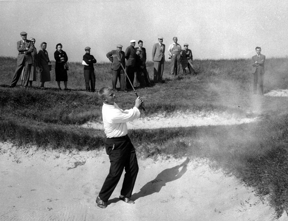 Jack Nicklaus, at 19 the youngest player in the British Amateur Golf Championship, blasts out of trap on 19th hole of his match round against Irishman Noel Fogarty in Sandwich, England, May 27, 1959. The ball landed an inch from the cup and the Ohio State student holed out in par four to win the extra hole and the match. At the time, Nicklaus was one of three U.S. Walker Cup 'Whiz Kids' who carried American hopes into fifth round of the tournament over the Royal St. George Course. (AP)