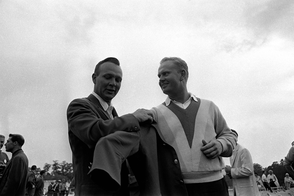 Arnold Palmer, left, 1964 Masters champion helps winner Jack Nicklaus into the traditional green jacket after Nicklaus' nine-stroke victory at Augusta National Golf Club, April 11, 1965. (GETTY IMAGES)