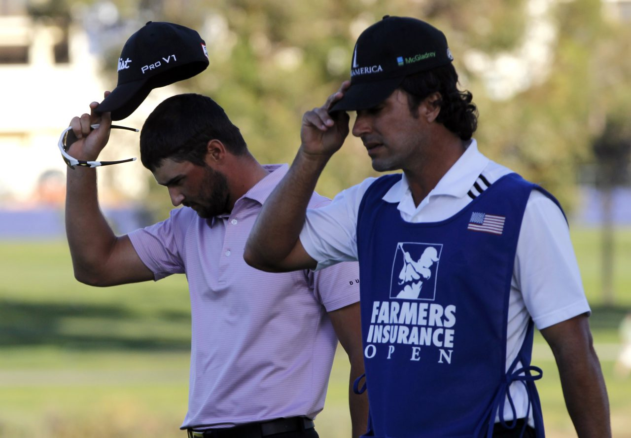 Kyle Stanley, left, and his caddie Brett Waldman walk off the 16th green where Stanley lost a playoff against Brandt Snedeker at the Farmers Insurance Open golf tournament on Sunday, Jan. 29, 2012, in San Diego. (AP Photo/Chris Carlson)