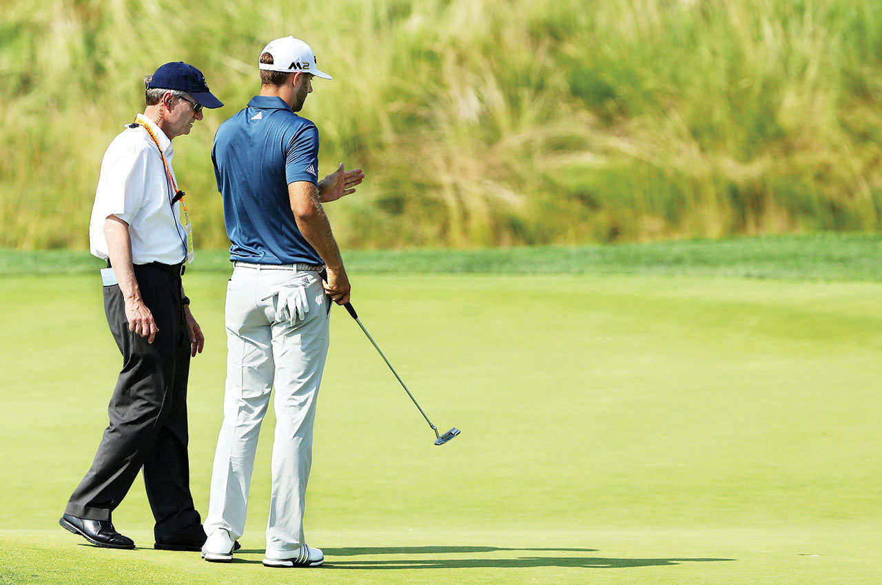 Dustin Johnson talks with USGA official Mark Newell after Johnson's ball moved on a green at Oakmont in the 2016 U.S. Open. Johnson was later handed a 1-shot penalty but won his first major championship anyways. (Getty Images/David Cannon)