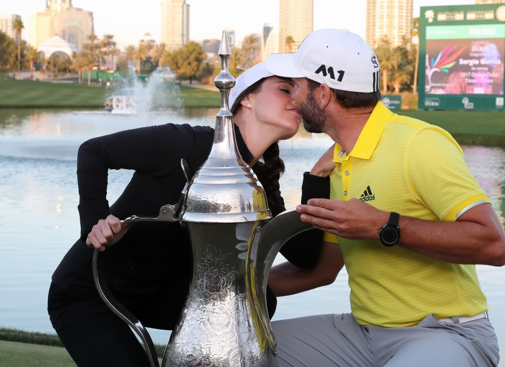 Sergio Garcia of Spain is congratulated by his girlfriend Angela Ankins, as he poses with the trophy following the final round of the Omega Dubai Desert Classic at the Emirates Golf Club, on February 5, 2017 in Dubai. / AFP / KARIM SAHIB (Photo credit should read KARIM SAHIB/AFP/Getty Images)