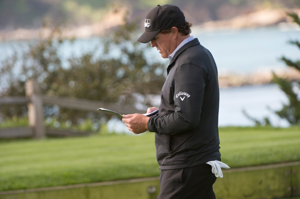 Feb 11, 2017; Pebble Beach, CA, USA; Phil Mickelson checks his yardage book at the 5th tee during the third round of the AT&T Pebble Beach Pro-Am golf tournament at Pebble Beach Golf Links. Mandatory Credit: Michael Madrid-USA TODAY Sports