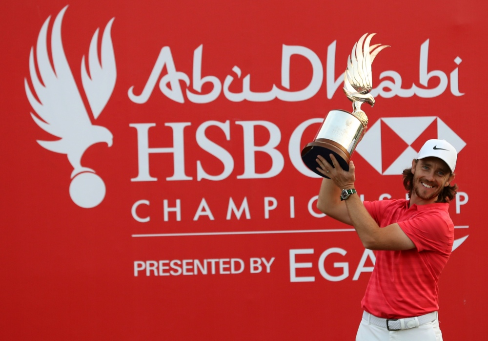 Tommy Fleetwood of England poses with the winner's trophy while celebrating his victory at the Abu Dhabi HSBC Golf Championship, at the Abu Dhabi Golf Club on January 21, 2018.
