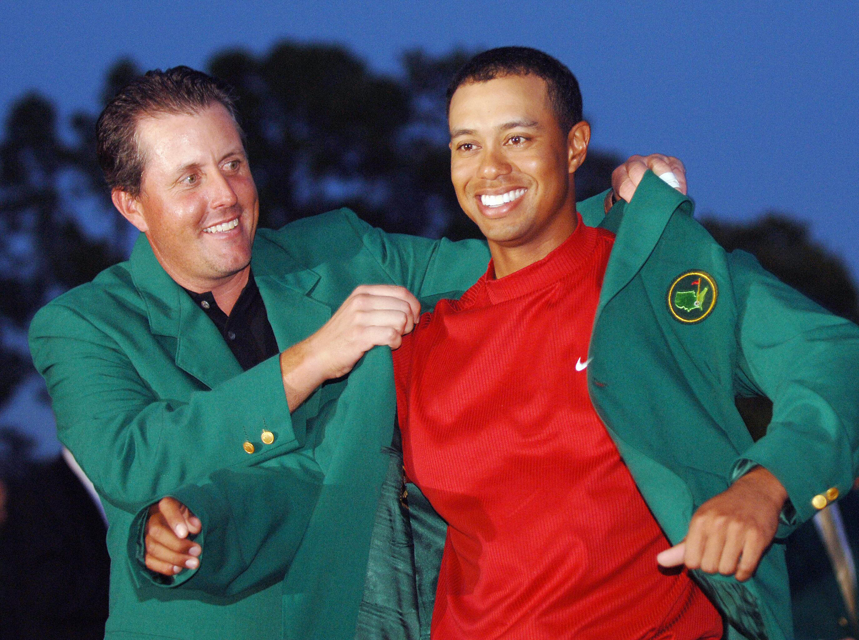 AUGUSTA, UNITED STATES: US golfer Tiger Woods (R) is awarded his green jacket by 2004 champion Phil Mickelson of the US at the 2005 Masters Golf Tournament Championship 10 April 2005 at the Augusta National Golf Club in Augusta, Ga. Woods claimed his 4th Masters title by defeating fellow American Chris DiMarco in a one-hole playoff. AFP PHOTO/Roberto SCHMIDT (Photo credit should read ROBERTO SCHMIDT/AFP/Getty Images)