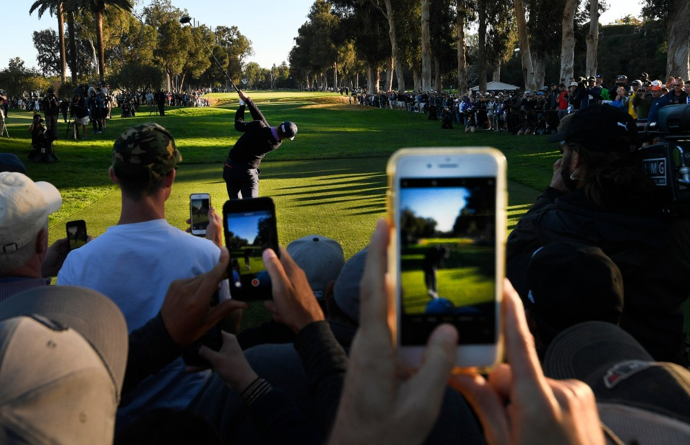 PACIFIC PALISADES, CA - FEBRUARY 15: Fans photograph Justin Thomas playing a tee shot on the 11th hole during the first round of the Genesis Open at Riviera Country Club on February 15, 2018 in Pacific Palisades, California. (Photo by Stan Badz/PGA TOUR)