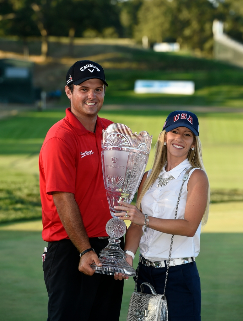 Patrick Reed holds The Barclays trophy together with his wife, Justine, after Reed won The Barclays golf tournament in Farmingdale, N.Y., Sunday, Aug. 28, 2016. (AP Photo/Kathy Kmonicek)