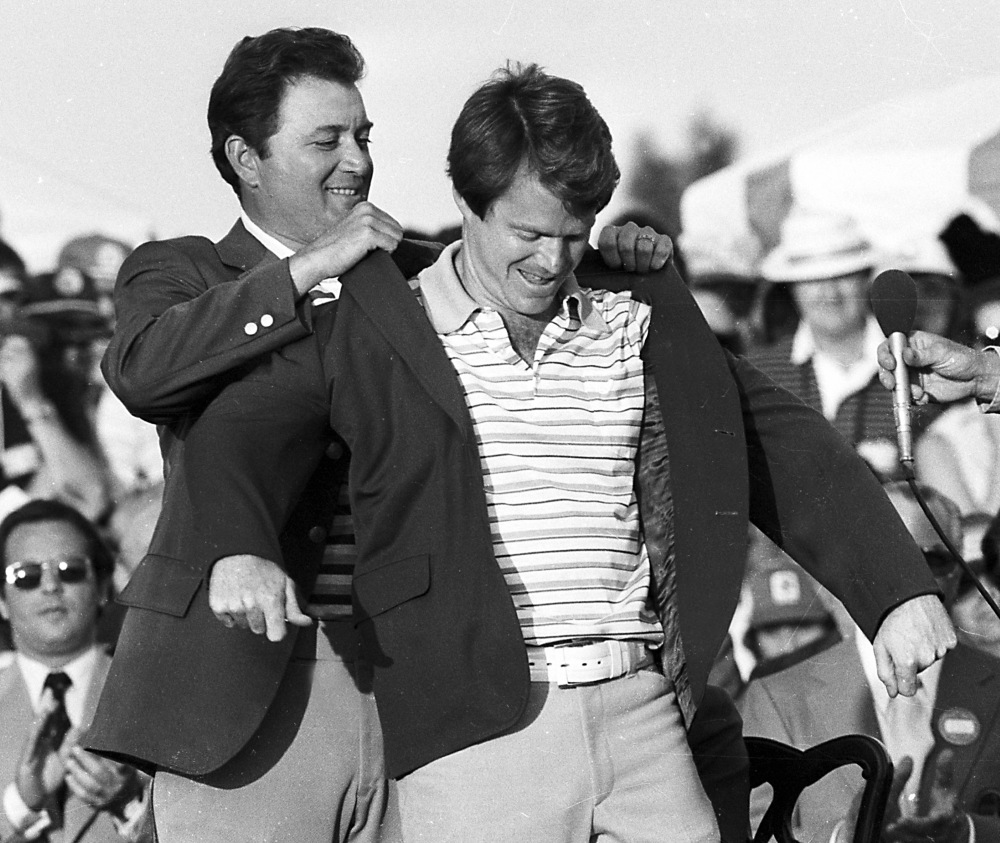 Tom Watson, winner of the Masters Golf Tournament, receives the traditional green coat from last year's champion Ray Floyd at the Augusta National Golf Club in Augusta, Ga., April 10, 1977. (AP Photo)
