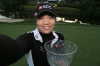 WILLIAMSBURG, VA - MAY 20: Ariya Jutanugarn of Thailand pretends to take a selfie while holding the trophy on the 18th green after winning the Kingsmill Championship presented by Geico on the River Course at Kingsmill Resort on May 20, 2018 in Williamsburg, Virginia. The tournament was shortened to three rounds due to inclement weather during round two. (Photo by Hunter Martin/Getty Images)