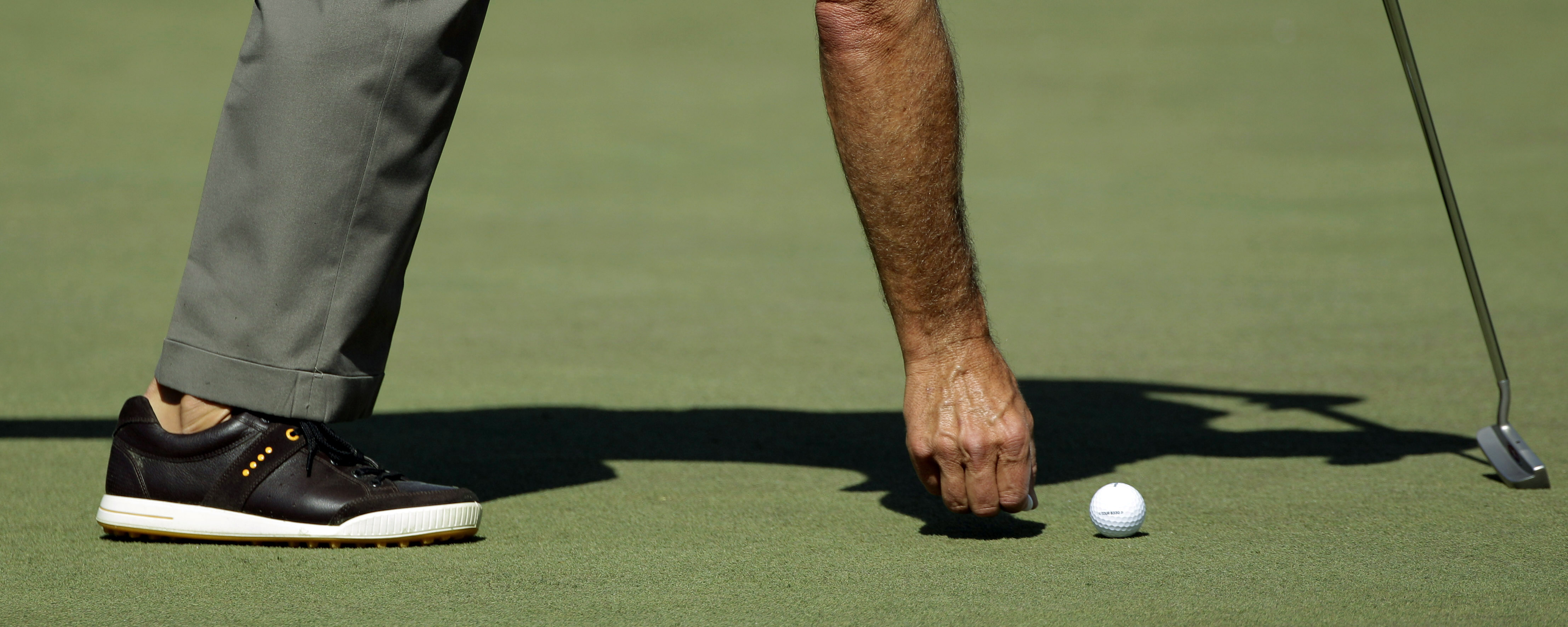Fred Couples picks up debris behind his ball on the second green during a practice round at the Masters golf tournament in Augusta, Ga., Tuesday, April 6, 2010. The tournament begins Thursday, April, 8. (AP Photo/Rob Carr)