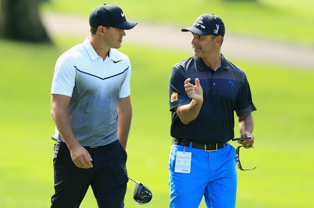 WESTBURY, NY - AUGUST 23:  Brooks Koepka of the USA walks with his coach Claude Harmon III during practice for The Northern Trust at Glen Oaks Club on August 23, 2017 in Westbury, New York.  (Photo by Andrew Redington/Getty Images)