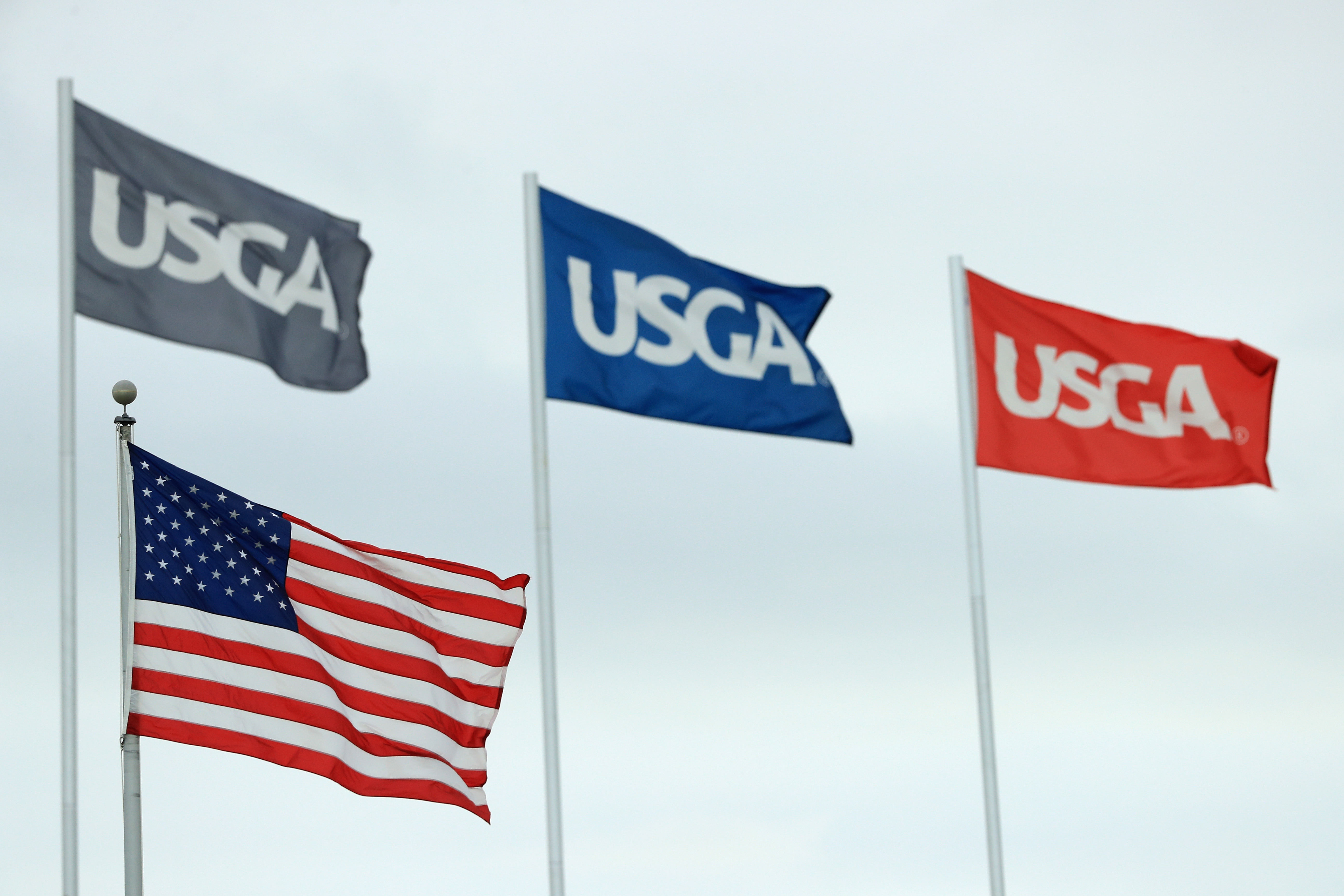 SOUTHAMPTON, NY - JUNE 15: An American flag and USGA flags blow in the breeze during the second round of the 2018 U.S. Open at Shinnecock Hills Golf Club on June 15, 2018 in Southampton, New York. (Photo by Andrew Redington/Getty Images)