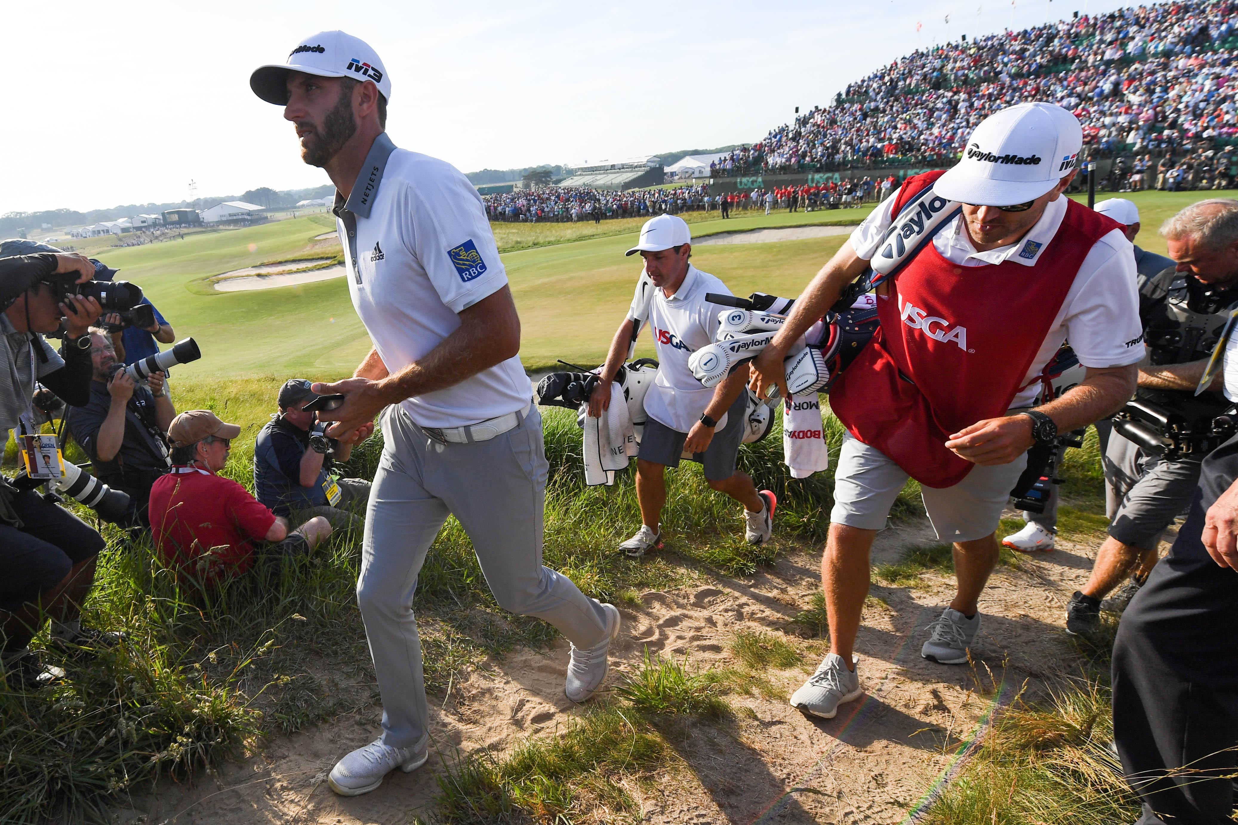 Jun 17, 2018; Southampton, NY, USA; Dustin Johnson walks off the eighteenth green after completing the final round of the U.S. Open golf tournament at Shinnecock Hills GC - Shinnecock Hills Golf C. Mandatory Credit: Shanna Lockwood-USA TODAY Sports
