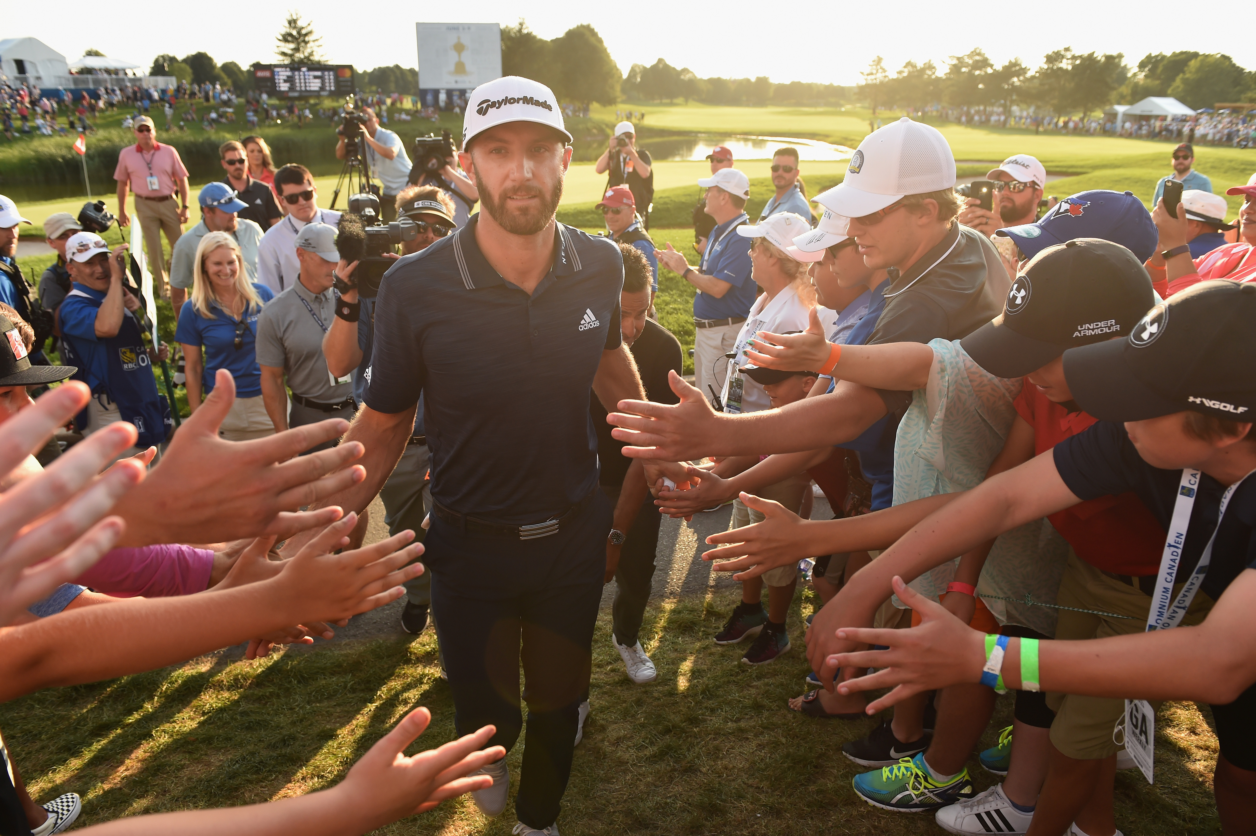 OAKVILLE, ON - JULY 29: Dustin Johnson celebrates his winning putt on the 18th hole by greeting fans Adam Scott of Australia Harris English exits the course during the final round at the RBC Canadian Open at Glen Abbey Golf Club on July 29, 2018 in Oakville, Canada. (Photo by Minas Panagiotakis/Getty Images)