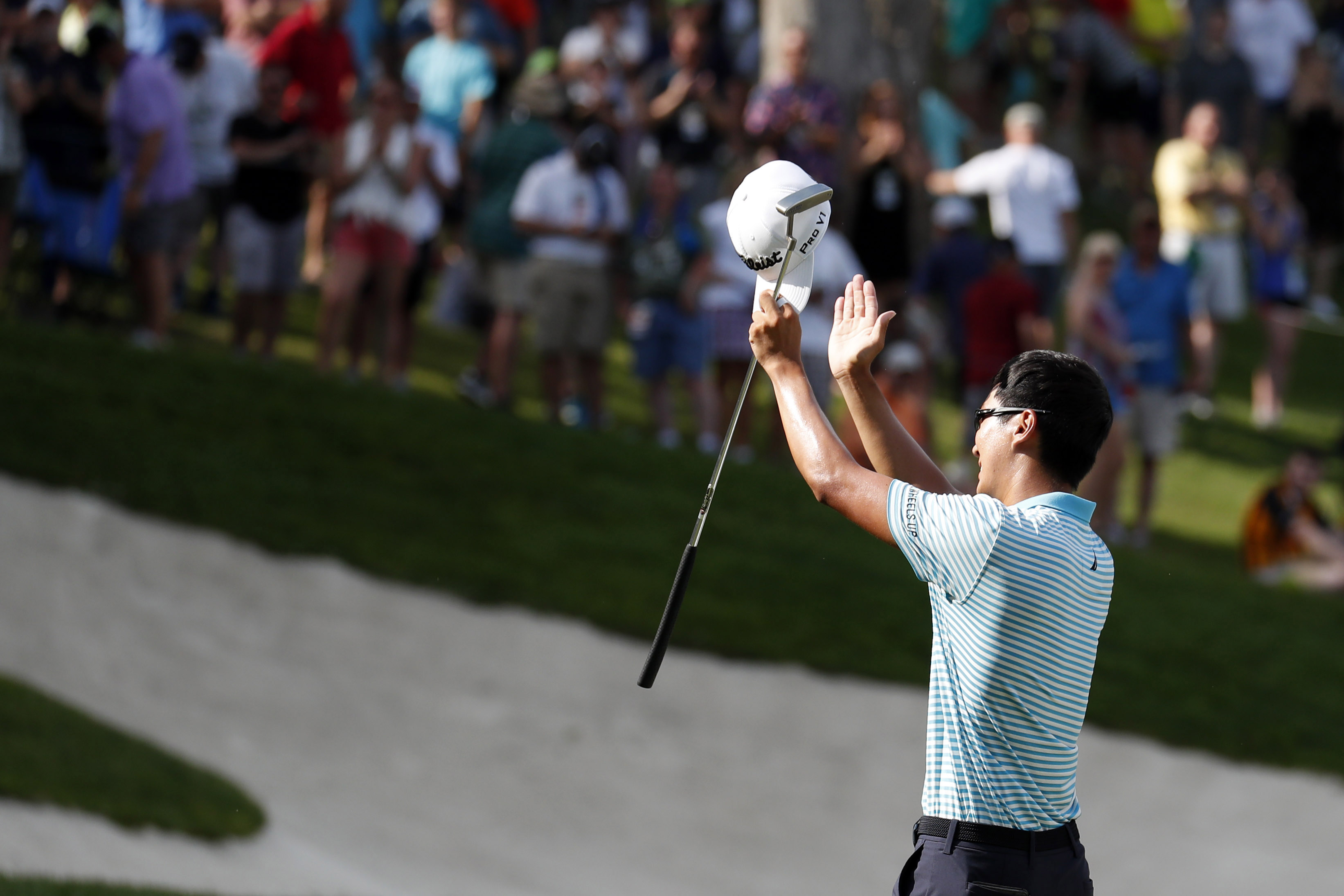 Jul 15, 2018; Silvis, IL, USA; PGA golfer Michael Kim acknowledges the fans on the 18th green after winning the John Deere Classic golf tournament at TPC Deere Run. Mandatory Credit: Brian Spurlock-USA TODAY Sports