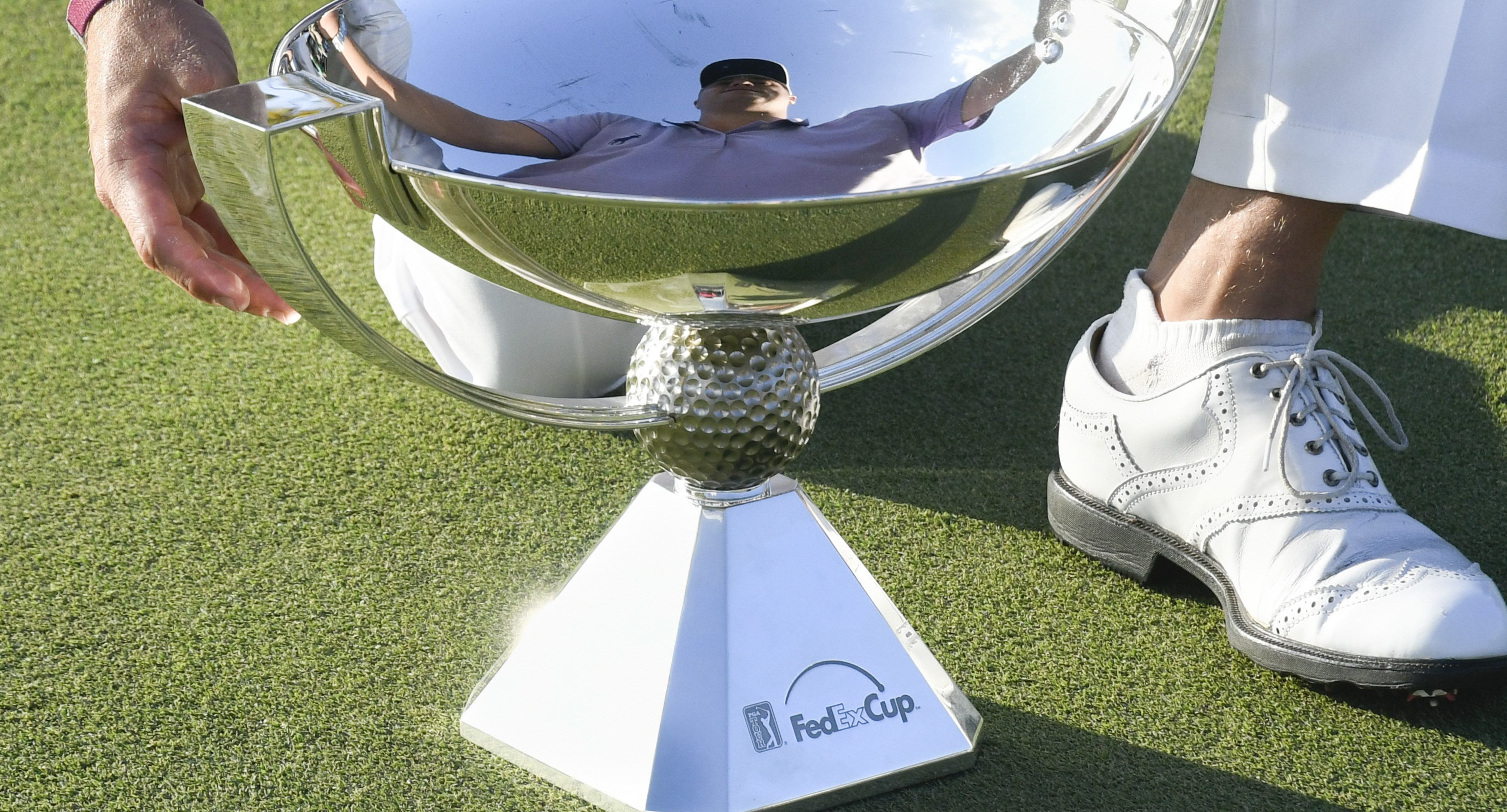 The image of Justin Thomas is reflected in the FedEx Cup as he goes to pick it up after winning it during the Tour Championship golf tournament at East Lake Golf Club in Atlanta, Sunday, Sept. 24, 2017, in Atlanta. (AP Photo/John Amis)