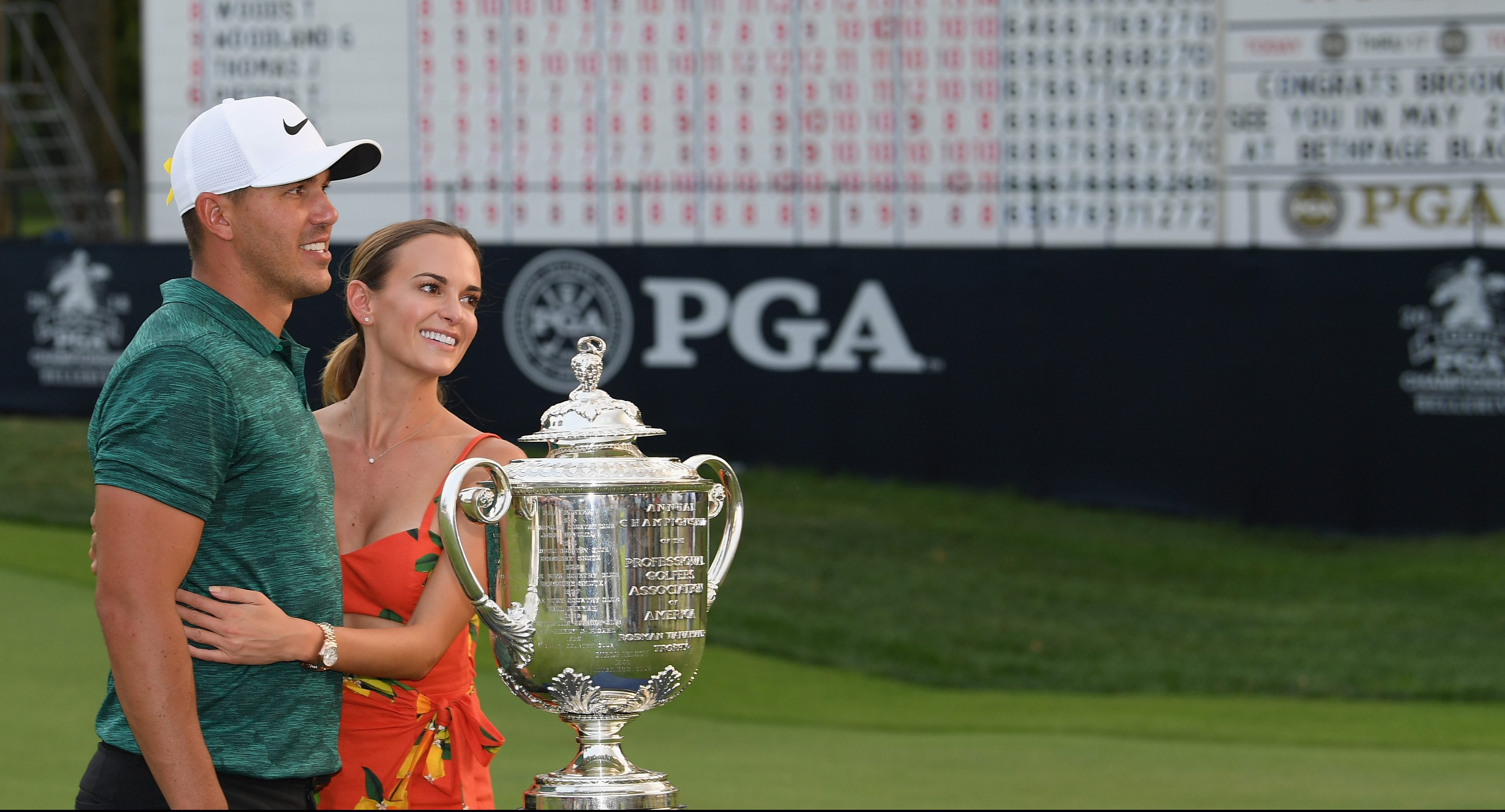 ST LOUIS, MO - AUGUST 12: Brooks Koepka of the United States poses with his girlfriend, Jena Sims, and the Wanamaker Trophy on the 18th green after winning the 2018 PGA Championship with a score of -16 at Bellerive Country Club on August 12, 2018 in St Louis, Missouri. (Photo by Ross Kinnaird/Getty Images)