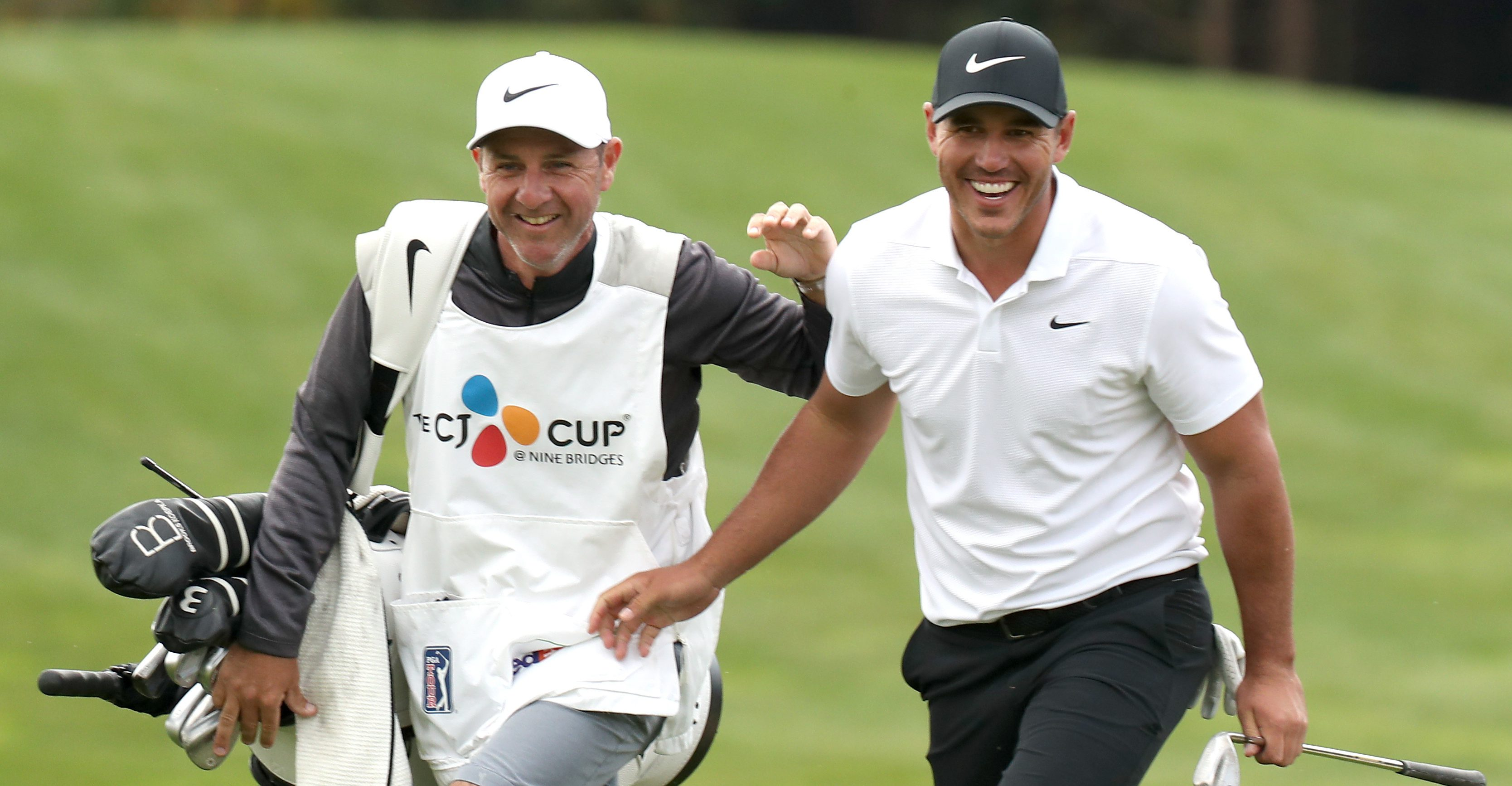 Brooks Koepka of the United States reacts with his caddie after his shot on the 16th hole during the final round of the CJ Cup PGA golf tournament at Nine Bridges on Jeju Island, South Korea, Sunday, Oct. 21, 2018. (Park Ji-ho/Yonhap via AP)