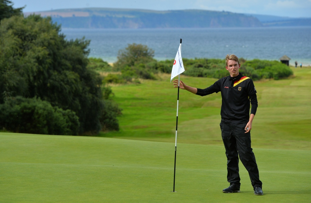 NAIRN, SCOTLAND - AUGUST 19 : Falko Hanisch of Germany tends the pin flag at the 14th green during the Semi Final match at the Boys Amateur Championship at Nairn Golf Club on August 19, 2017 in Nairn, Scotland. (Photo by Mark Runnacles/R&A/R&A via Getty Images)