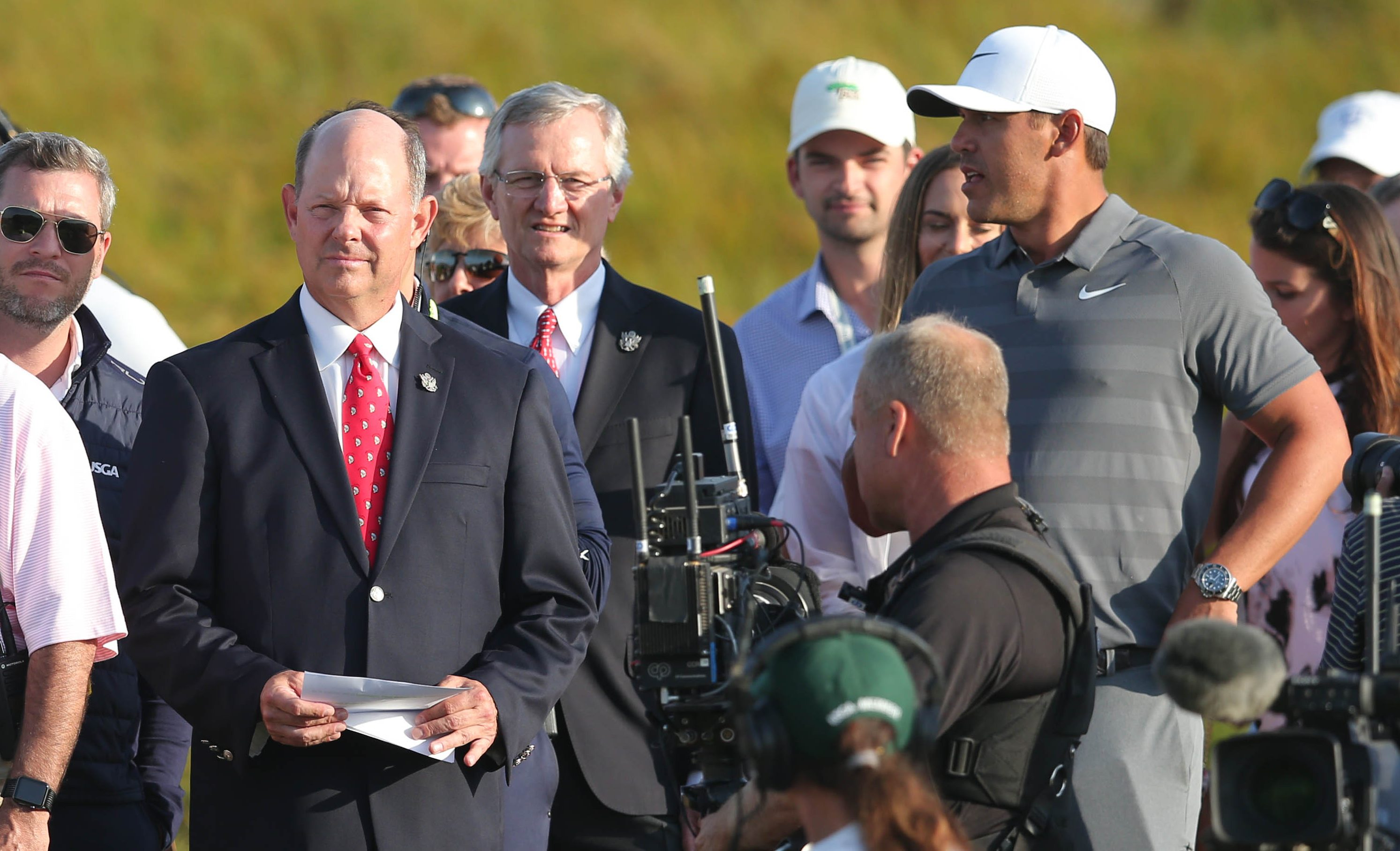 Jun 17, 2018; Southampton, NY, USA; USGA executive director Mike Davis and Brooks Koepka arrive on the eighteenth green for the trophy presentation after the final round of the U.S. Open golf tournament at Shinnecock Hills GC - Shinnecock Hills Golf C. Mandatory Credit: Brad Penner-USA TODAY Sports