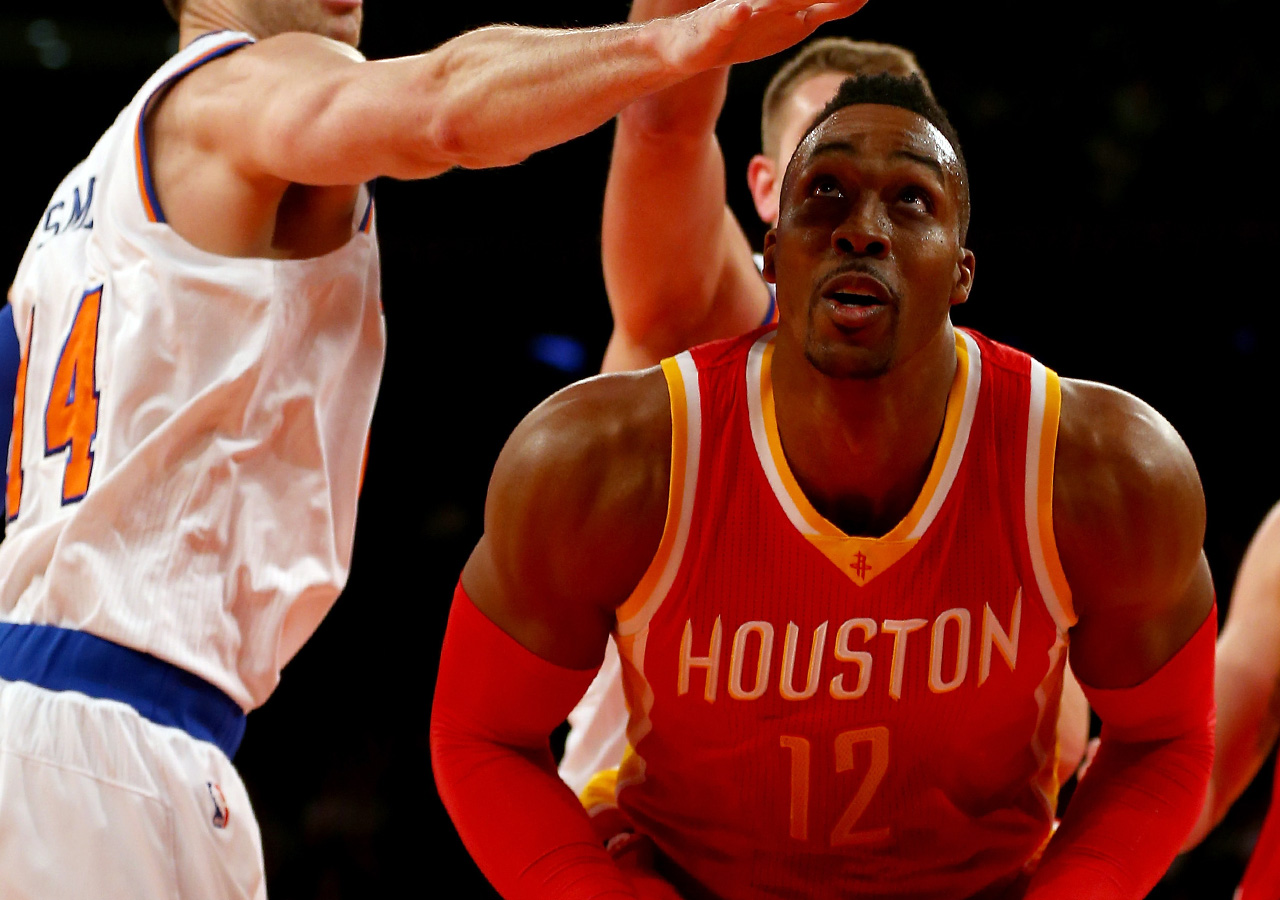 NEW YORK, NY - JANUARY 08:  Dwight Howard #12 of the Houston Rockets heads for the net as Jason Smith #14 of the New York Knicks defends at Madison Square Garden on January 8, 2015 in New York City. NOTE TO USER: User expressly acknowledges and agrees that, by downloading and/or using this photograph, user is consenting to the terms and conditions of the Getty Images License Agreement.  (Photo by Elsa/Getty Images)
