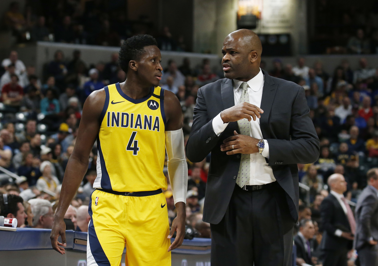 Victor Oladipo and Nate McMillan chatting during a game