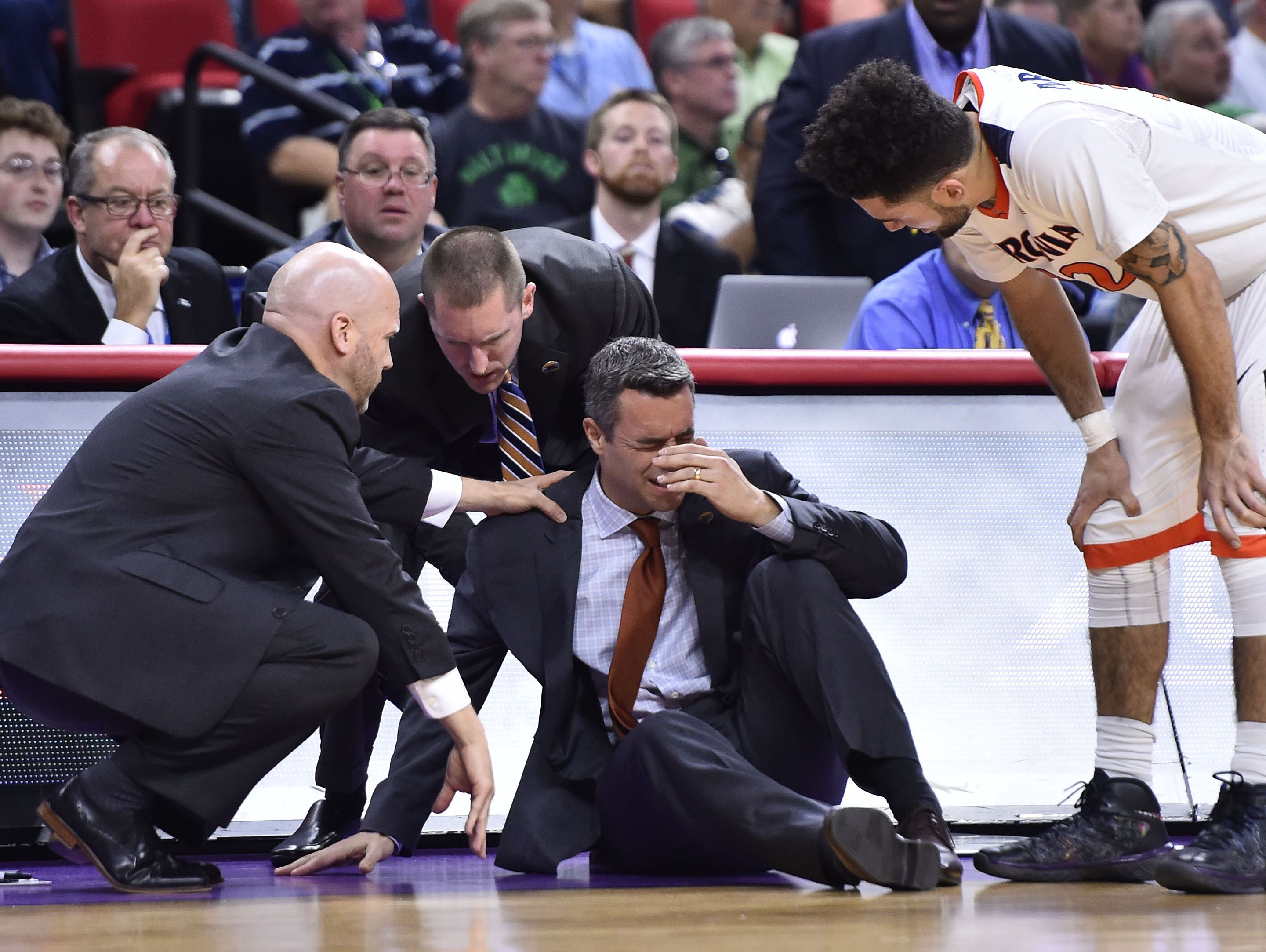 Virginia Cavaliers assistant athletic director Ronnie Wideman (C) and assistant coach Brad Soderberg (L) tends to head coach Tony Bennett, who fainted in front of guard London Perrantes (32) during the first half at PNC Arena.