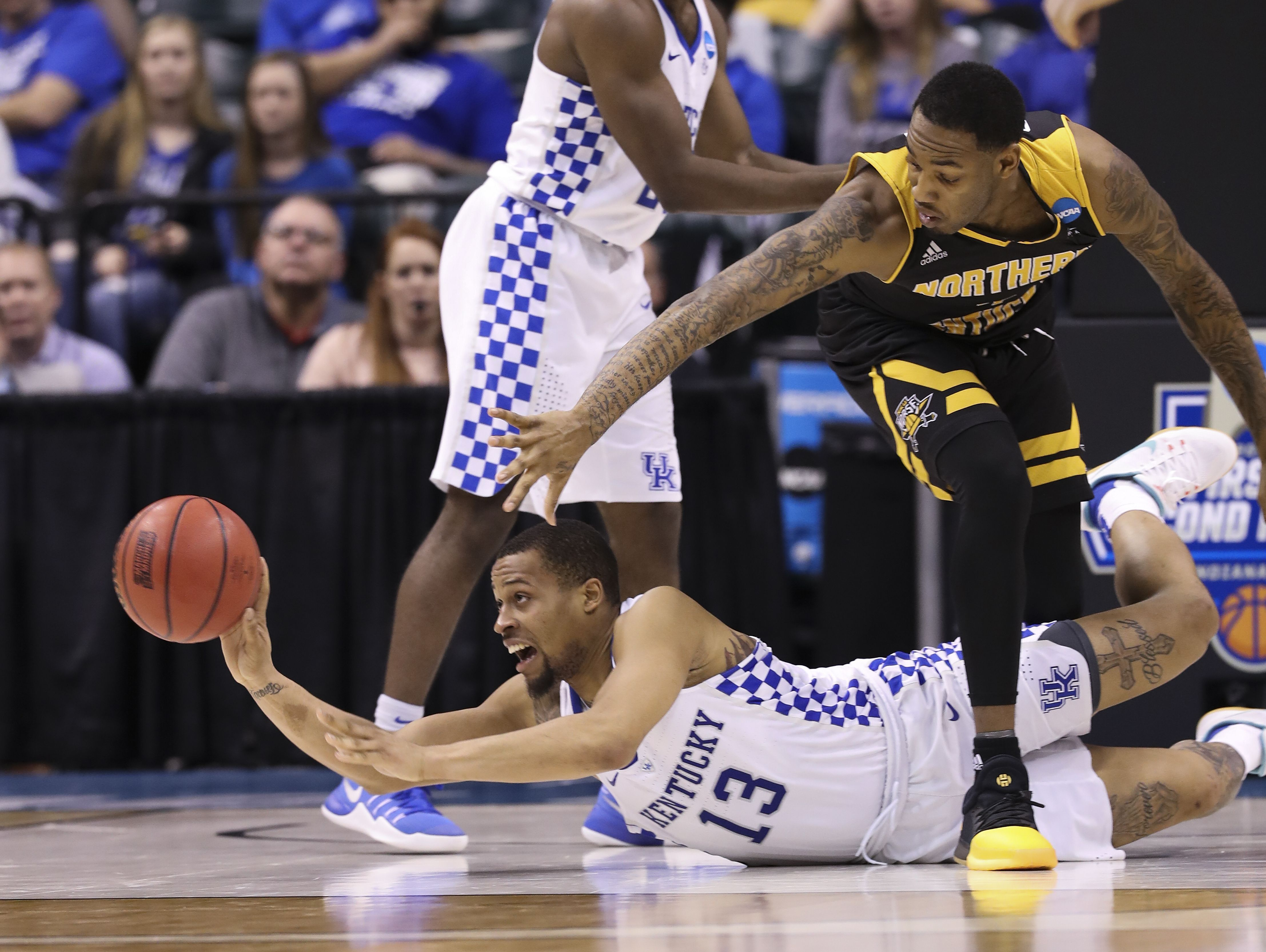 UK's Isaiah Briscoe (13) passed as he was tied up NKU's Jeff Garrett (4) during the NCAA tournament at the Bankers Life Fieldhouse in Indianapolis. Mar. 17, 2017