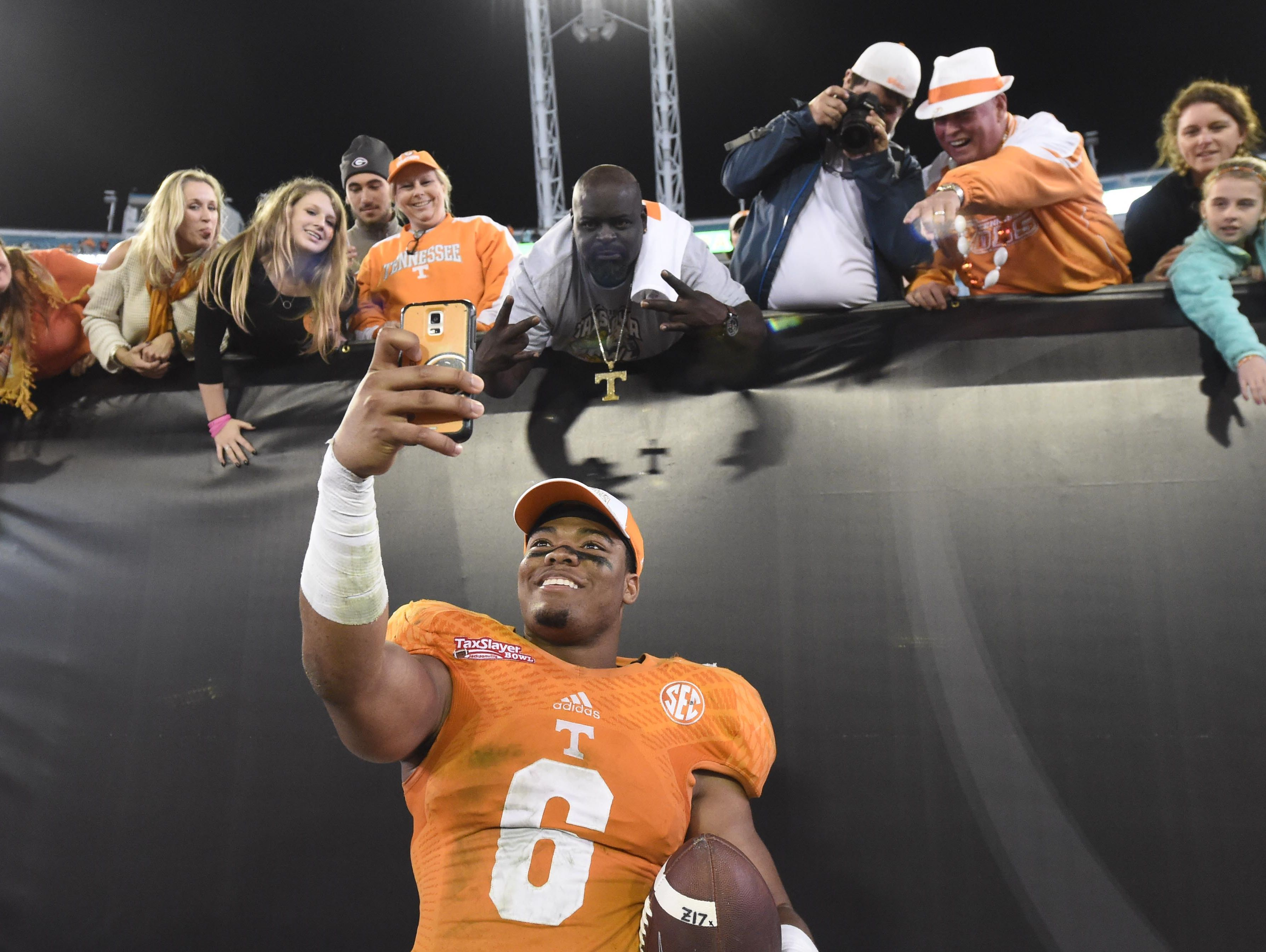 Tennessee defensive back Todd Kelly Jr. (6) obliges a fan's request to take a selfie with his smartphone following Tennessee's 45-28 victory over Iowa in the Taxslayer Bowl at EverBank Field on Friday, Jan. 2, 2015 in Jacksonville, Fla.