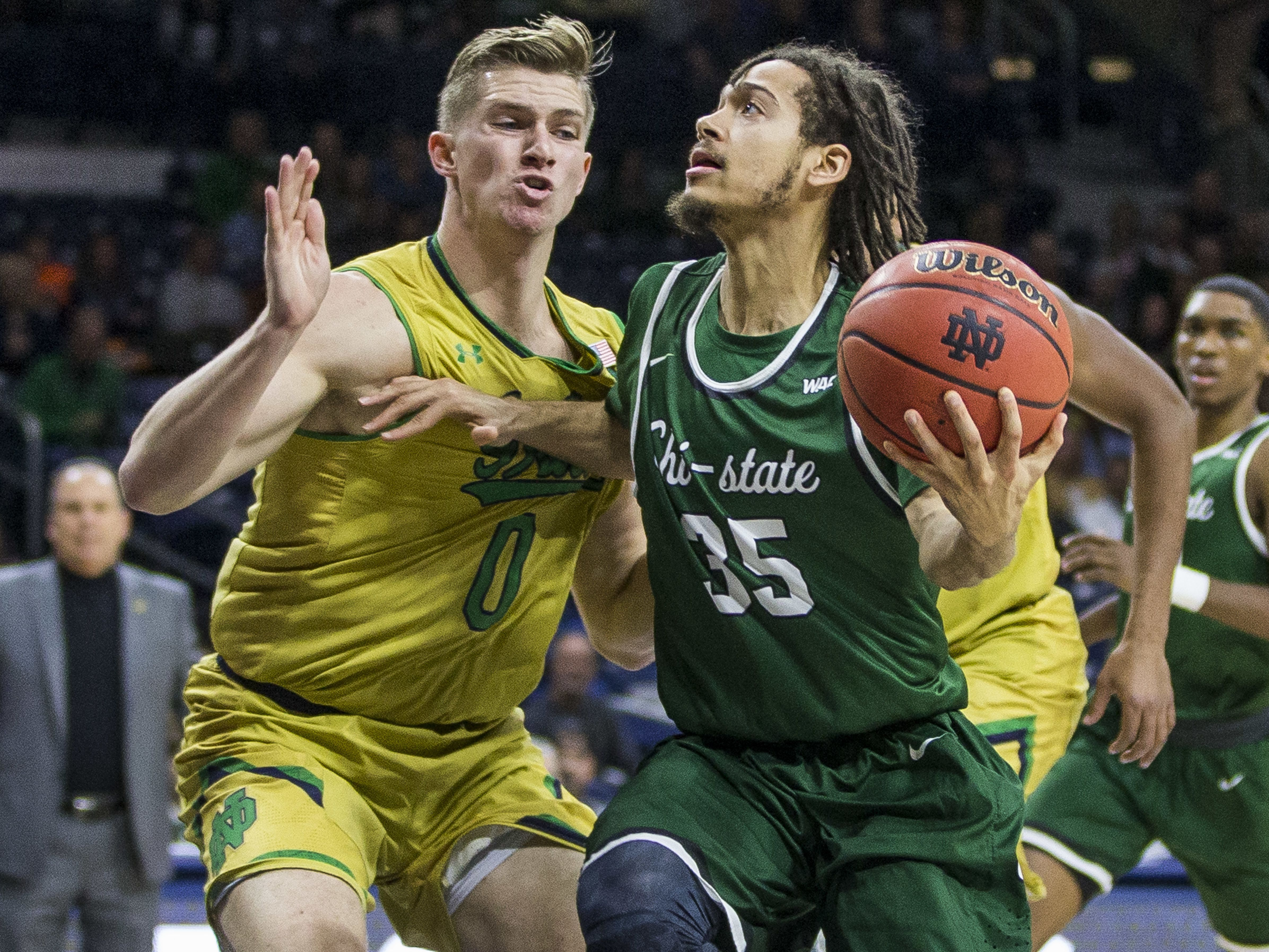Chicago State's Rob Shaw (35) drives by Notre Dame's Rex Pflueger (0) during the first half of an NCAA college basketball game Thursday, Nov. 16, 2017, in South Bend, Ind. (AP Photo/Robert Franklin)