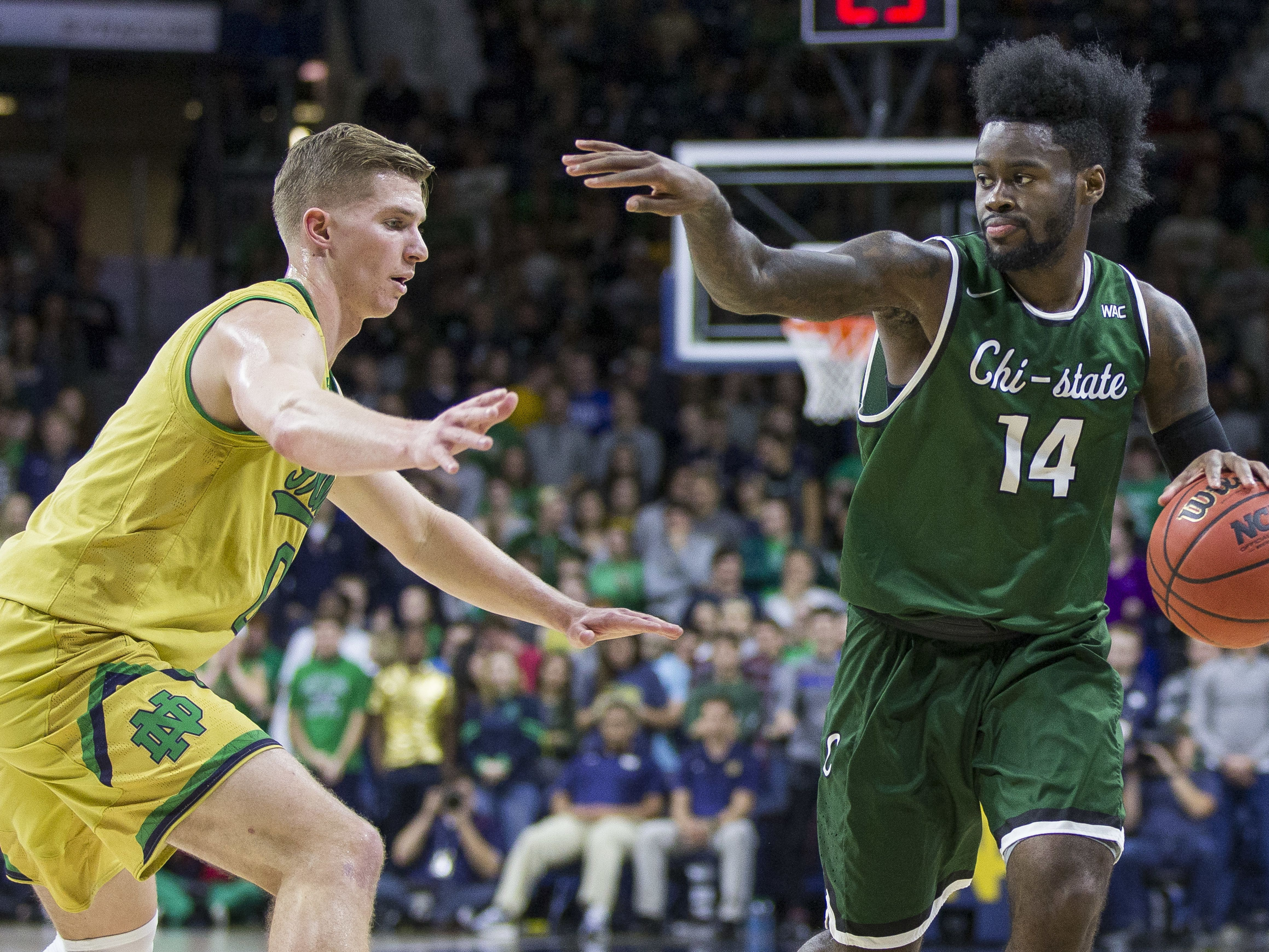 Chicago State's Fred Sims, Jr. (14) motions to a teammate as he moves by Notre Dame's Rex Pflueger (0) during the first half of an NCAA college basketball game Thursday, Nov. 16, 2017, in South Bend, Ind. (AP Photo/Robert Franklin)