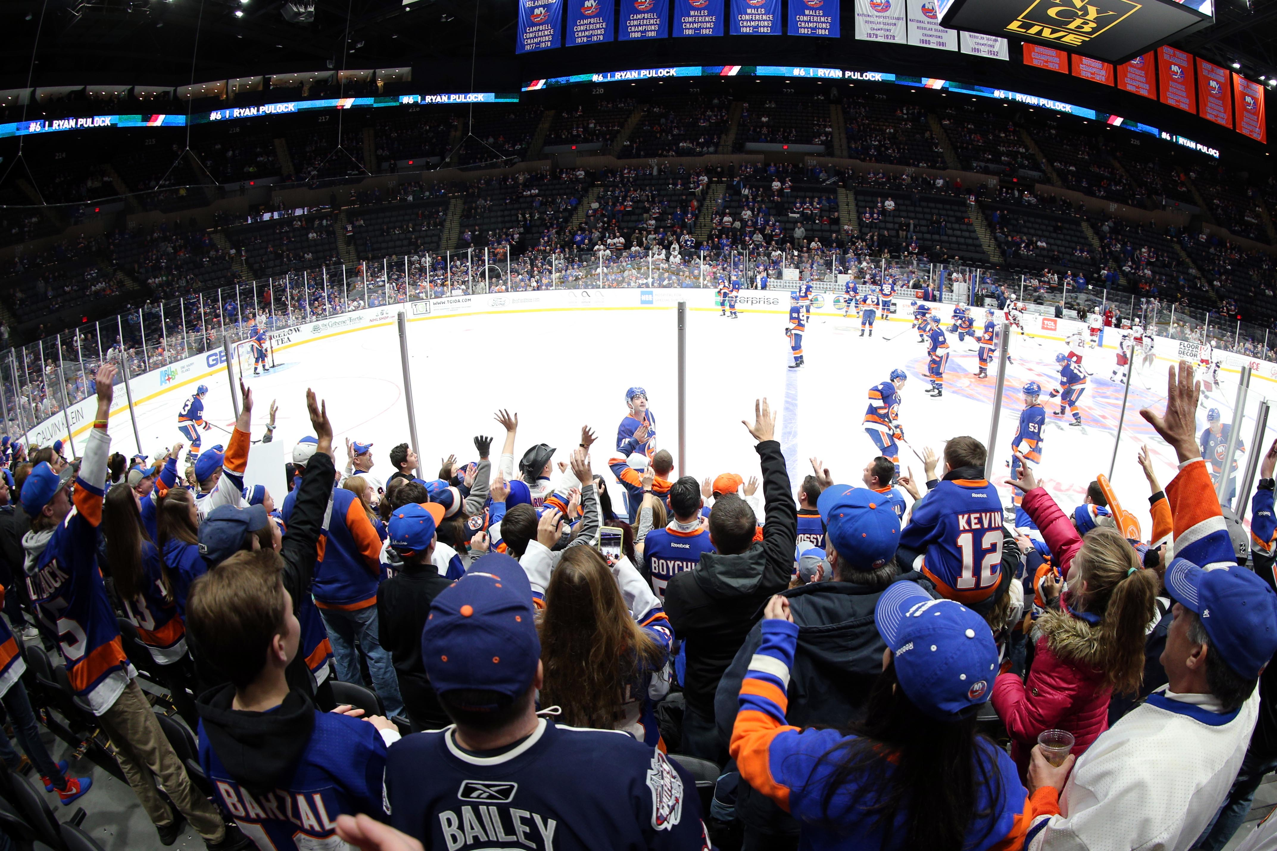 Dec 1, 2018; Uniondale, NY, USA; New York Islanders right wing Cal Clutterbuck (15) tosses a puck to fans during warmups before a game against the Columbus Blue Jackets at Nassau Veterans Memorial Coliseum. Mandatory Credit: Brad Penner-USA TODAY Sports